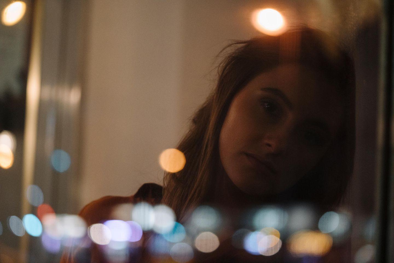Frau lehnt melancholisch an Fenster