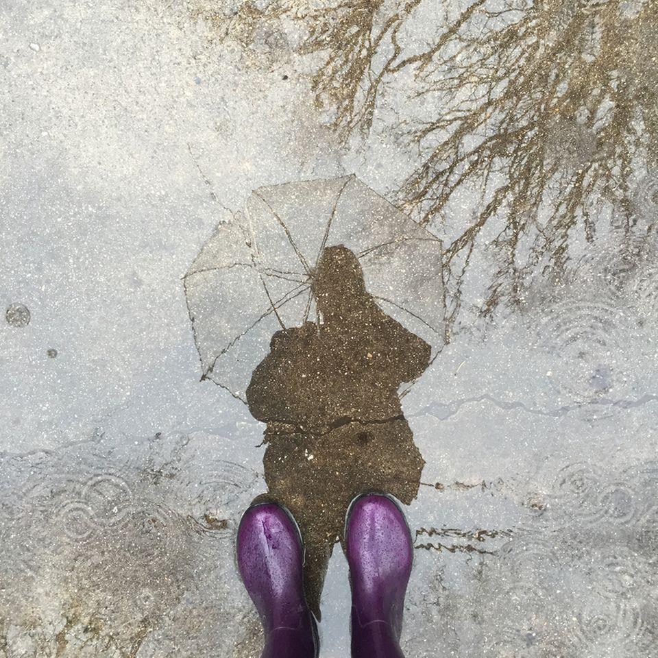 Selbsterkenntnis: Spiegelbild einer Person in einer Pfütze