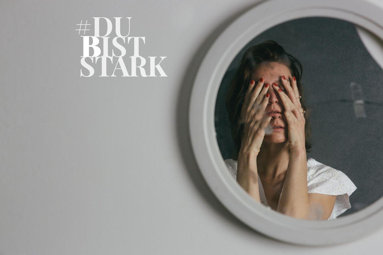 Dr. Astrid Freisen: Frau steht mit Händen vorm Gesicht vor Spiegel