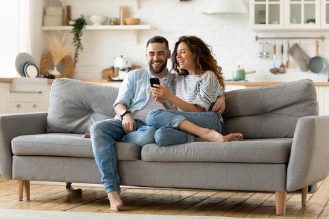 Paar auf dem Sofa beim Online-Shopping mit Gutschein