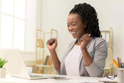 Glückliche Frau beim Online-Shopping auf eBay mit Gutschein