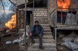 World Press Photo: Mann sitzt vor brennendem Haus