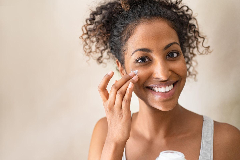 Schöne Frau benutzt Creme im Gesicht