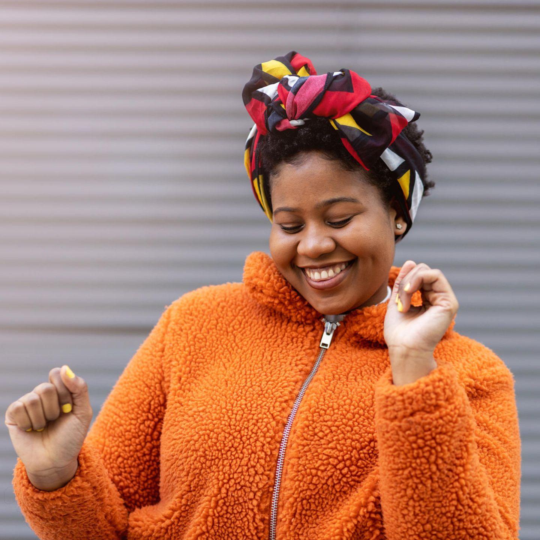 Horoskop: Eine fröhliche junge Frau tanz vor einer weißen Wand