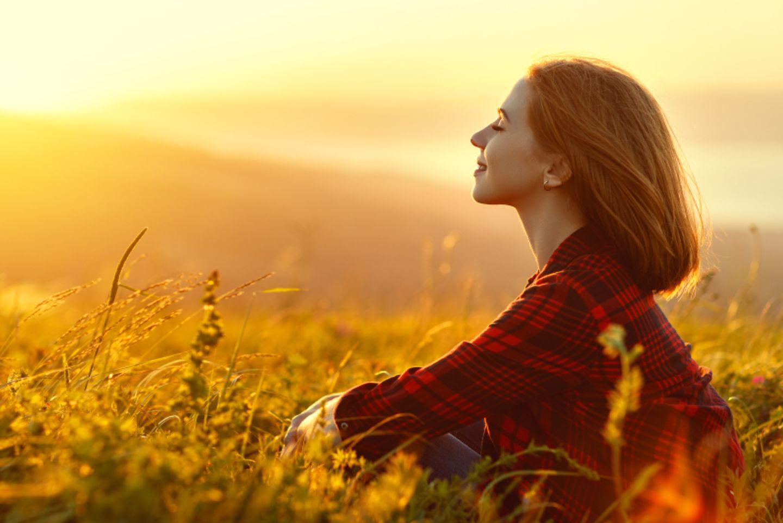 Selbstfindung: Frau sitzt in einem Feld vorm Sonnenuntergang
