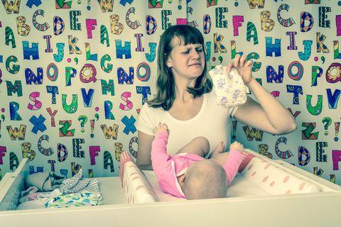 Windelfrei: Eine Mutter wickelt ihr Baby und rümpft die Nase wegen der vollen Windel