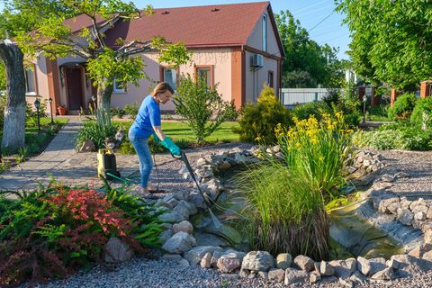 Gartenteich anlegen: Mit wenigen Handgriffen zum Paradies, Frau bewässert Gartenteich