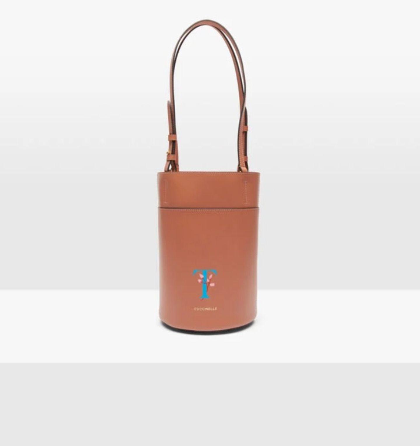 """Ich liebe Pieces, die ich personalisieren lassen kann. Es ist ein tolles Gefühlzu wissen, dass diese Tasche nicht unbedingt jede:r trägt. Denn mit (m)einem handbemalten Buchstaben vorne drauf, mache ich sie zu etwas ganz Besonderem. """"Garconne Mini"""", von Coccinelle, kostet ca. 250 Euro."""