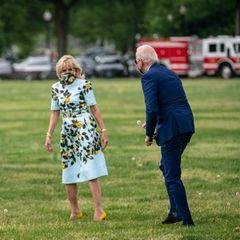 """Was für ein süßes Foto! Auf dem Weg zum Flugzeug scheint Präsident Joe Biden so hin und weg von seiner Ehefrau zu sein, dass er spontan einGänseblümchen pflückt und es seiner Gattin feierlich überreicht. Verständlich! Denn Dr. Jill Biden sieht in ihrem Lemon-Kleid einfach hinreißend aus. Das Kleid scheint ein Liebling im Kleiderschrank der First Lady zu sein, denn bereits ein paar Wochen vorher bei den """"International Women of Courage Awards"""" griff sie zu dem Oscar de la Renta-Kleid."""