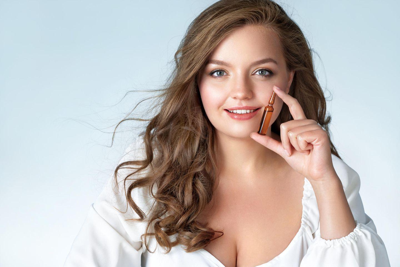 Schöne Frau hält Beauty Ampulle vor ihr Gesicht