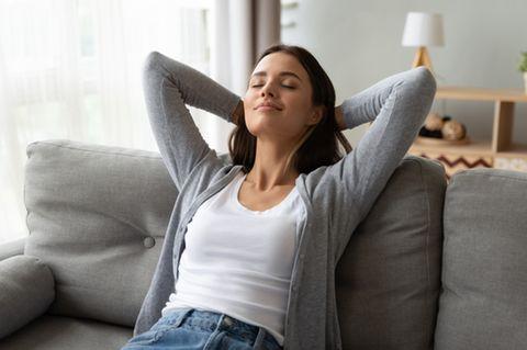 Sisu: Frau sitzt zufrieden auf der Couch.