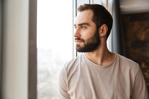 Männlichkeit: Mann schaut aus dem Fenster