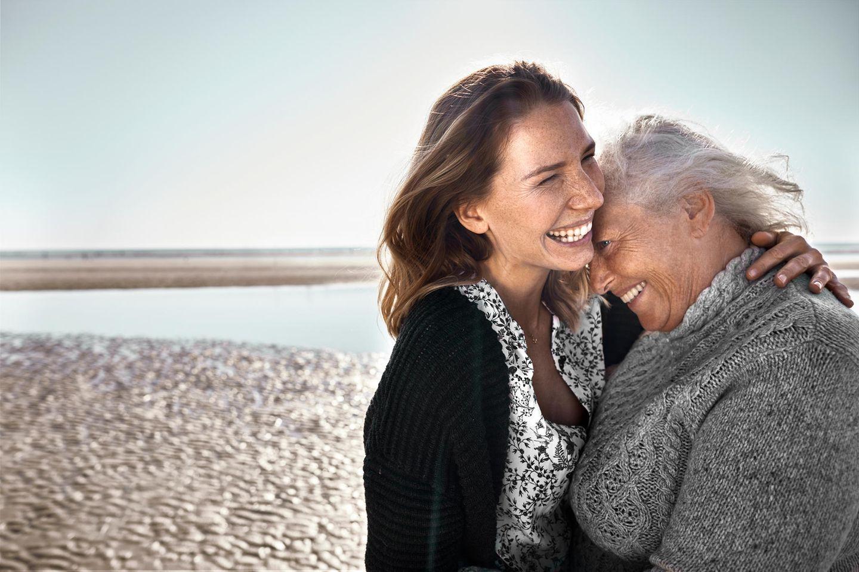 Tochter umarmt Mutter am Strand