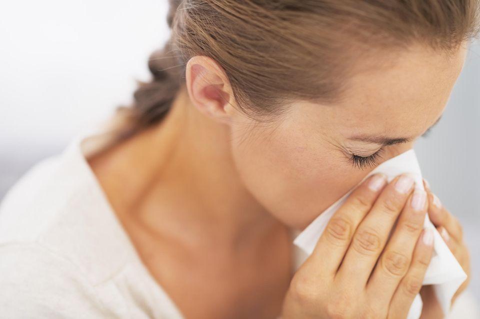 Allergie während Corona: Frau putzt ihre Nase
