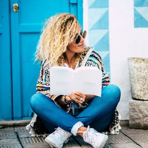 Psychologie: Eine fröhliche Frau sitzt vor der Tür und liest