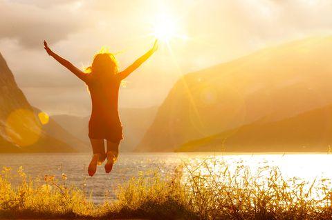 Horoskop: Eine Frau springt fröhlich in die Höhe