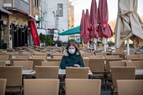 Corona aktuell: Frau mit Maske in der Außen-Gastronomie