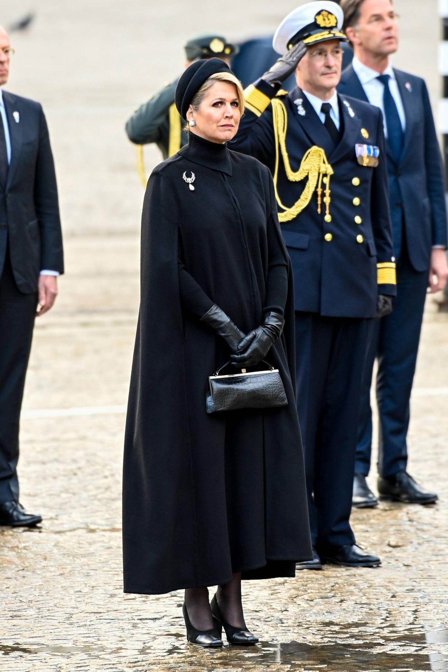 Königin Máxima der Niederlande liebt normalerweise farbenfrohe Styles, gerne auffällig und mit Mustern. In Amsterdam besucht siezusammen mit ihrem Mann Willem-Alexander eine Gedenkfeierund entscheidet sich diesmal aufgrund desAnlasses des Totengedenktages für einen Komplett-Look in Schwarz. Sie trägt ein figurbetontes Kleid von Massimo Dutti und darüber einen Cape-Mantel. Beides lässt sie sehr elegant wirken. Bei Schuhen und Accessoiresentscheidetsie sich ebenfalls fürTon-in-Ton und beweist erneut wahres Stilgefühl.