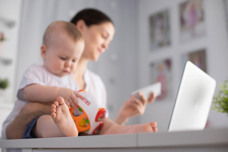 Sorgearbeit: Frau arbeitet und kümmert sich um Baby