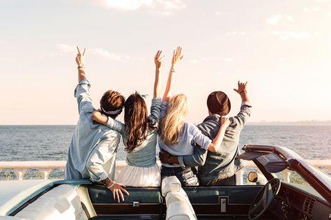 Lebenssprüche: Freunde feiern am Meer.