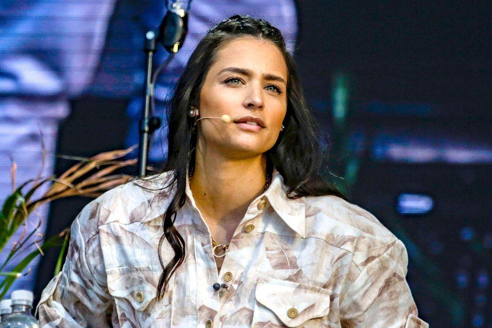 Amira Pocher: Ihr Start in Deutschland war alles andere als leicht: Amira Pocher schaut ernst auf der Bühne