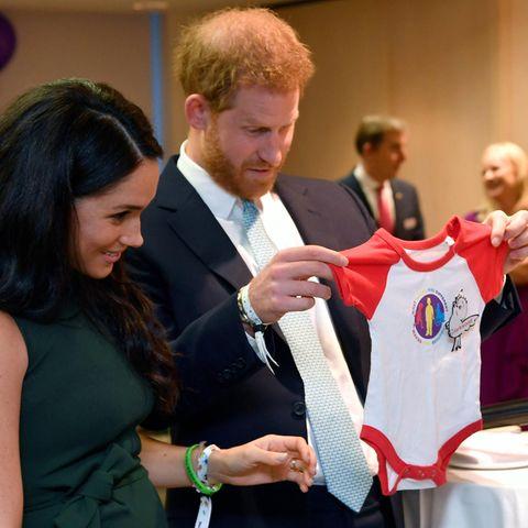 Herzogin Meghan + Prinz Harry: Dieser Titel steht ihrer Tochter zu: Beide stehen nebeneinander, Prinz Harry hält Strampler