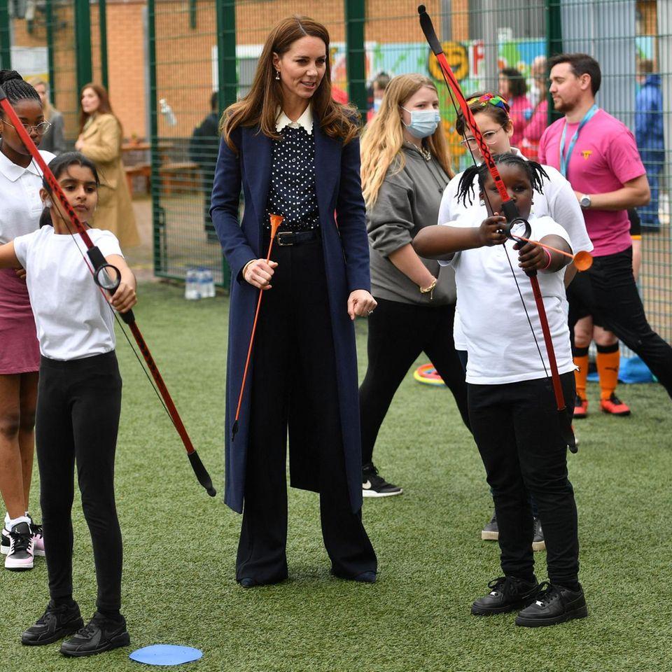 Bei einem Termin im Rahmen der Woche für mentale Gesundheit zeigt Herzogin Catherine mal wieder eine ganz neue Style-Facette: Sie tauscht Kleider gegen eine ausgestellte Hose, Pünktchenbluse und langen Mantel. Sehr schick!