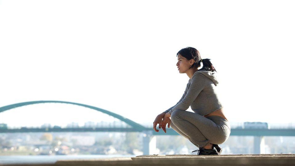 Horosokop: Eine sportliche Frau vor einer Brücke