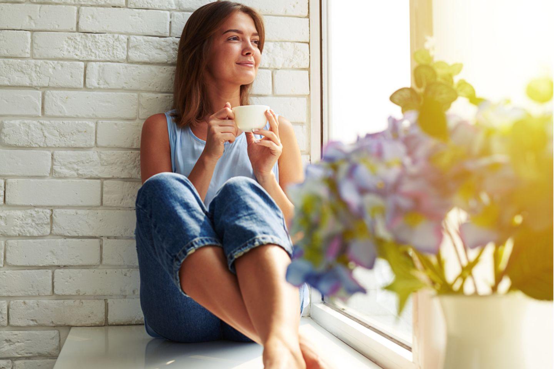 Sprüche zum Nachdenken: Frau sitzt am Fenster und trinkt Tee.