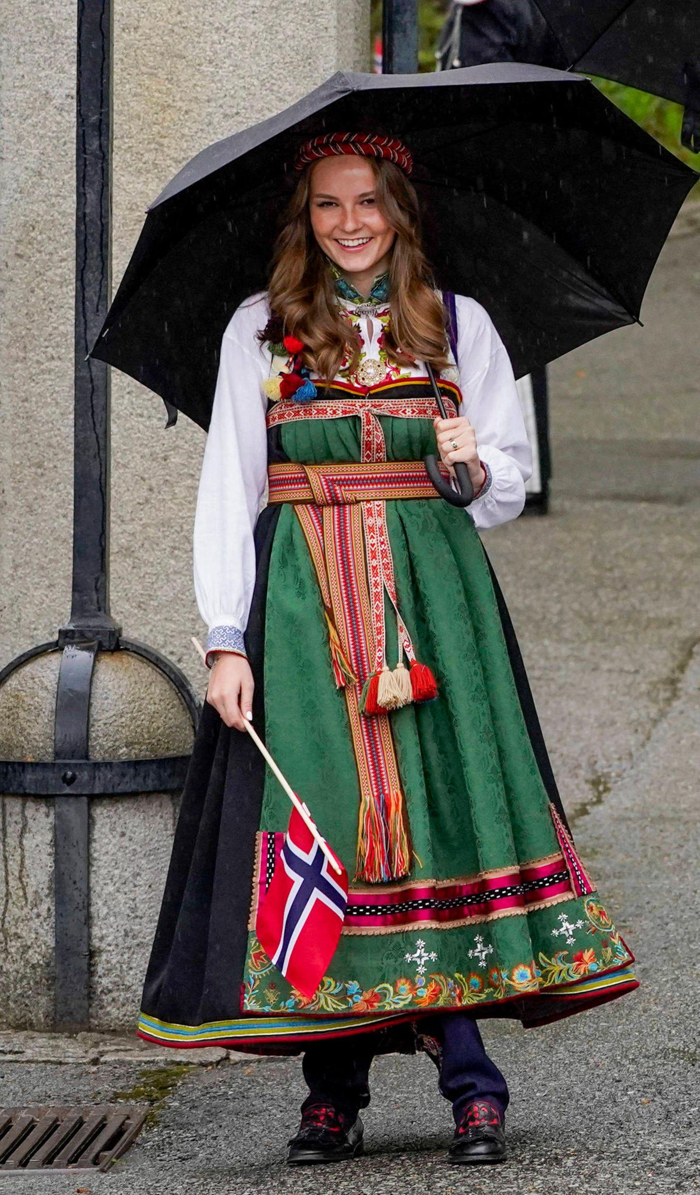 """Am 17. Mai feiert Norwegen seinen Nationalfeiertag, wobei die Feier in diesem Jahr aufgrund der Pandemie kleiner ausfällt. Doch die Outfits der norwegischen Königsfamilie sind mindestens so opulent wie die Jahre zuvor. Besonders hübsch anzusehen ist das Kleid der 17-jährigen Royal.Die Robe trägt den Namen """"Bunad"""" und ist ein Geschenk von ihren Großeltern Königin Sonja und König Harald. Das traditionelle Kleidungsstück stammt aus Aust-Telemark und erinnert an die Trachten, die schon um das Jahr 1810 von den norwegischen Frauen getragen wurden."""