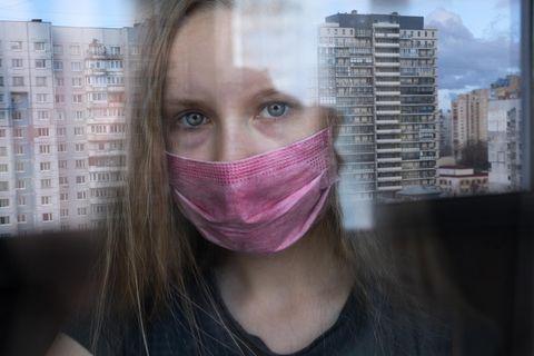Corona aktuell: Frau mit Maske im Hochhaus