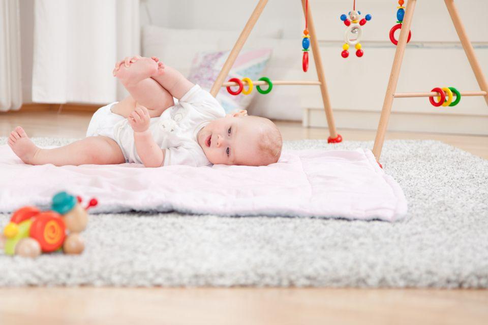 Babyzimmer einrichten: Baby auf einer Decke auf dem Boden