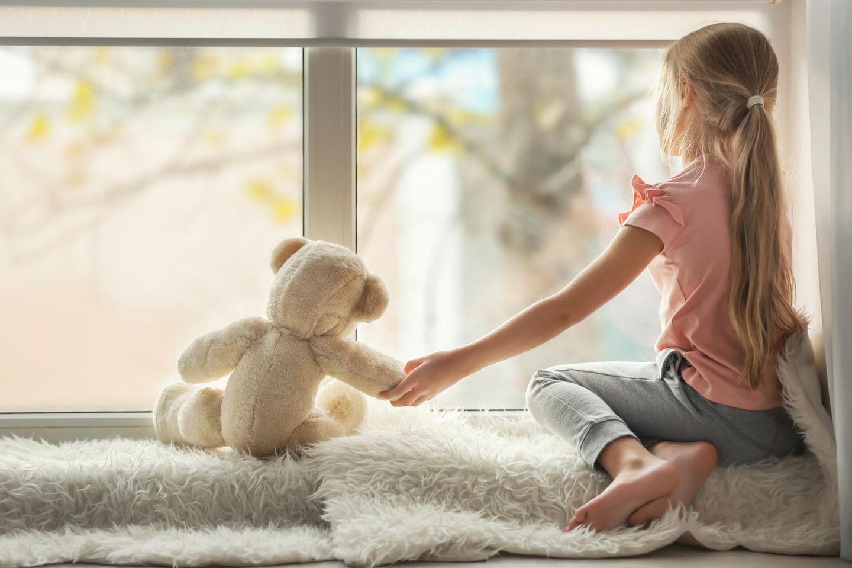 Kinderärzt:innen warnen: Mädchen sitzt vor einem Fenster