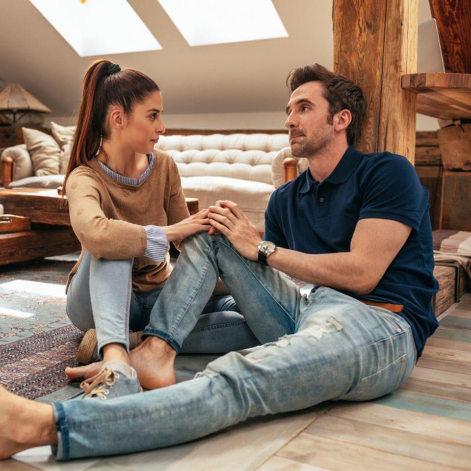 Beziehungsfragen: Paar sitzt auf dem Boden und unterhält sich