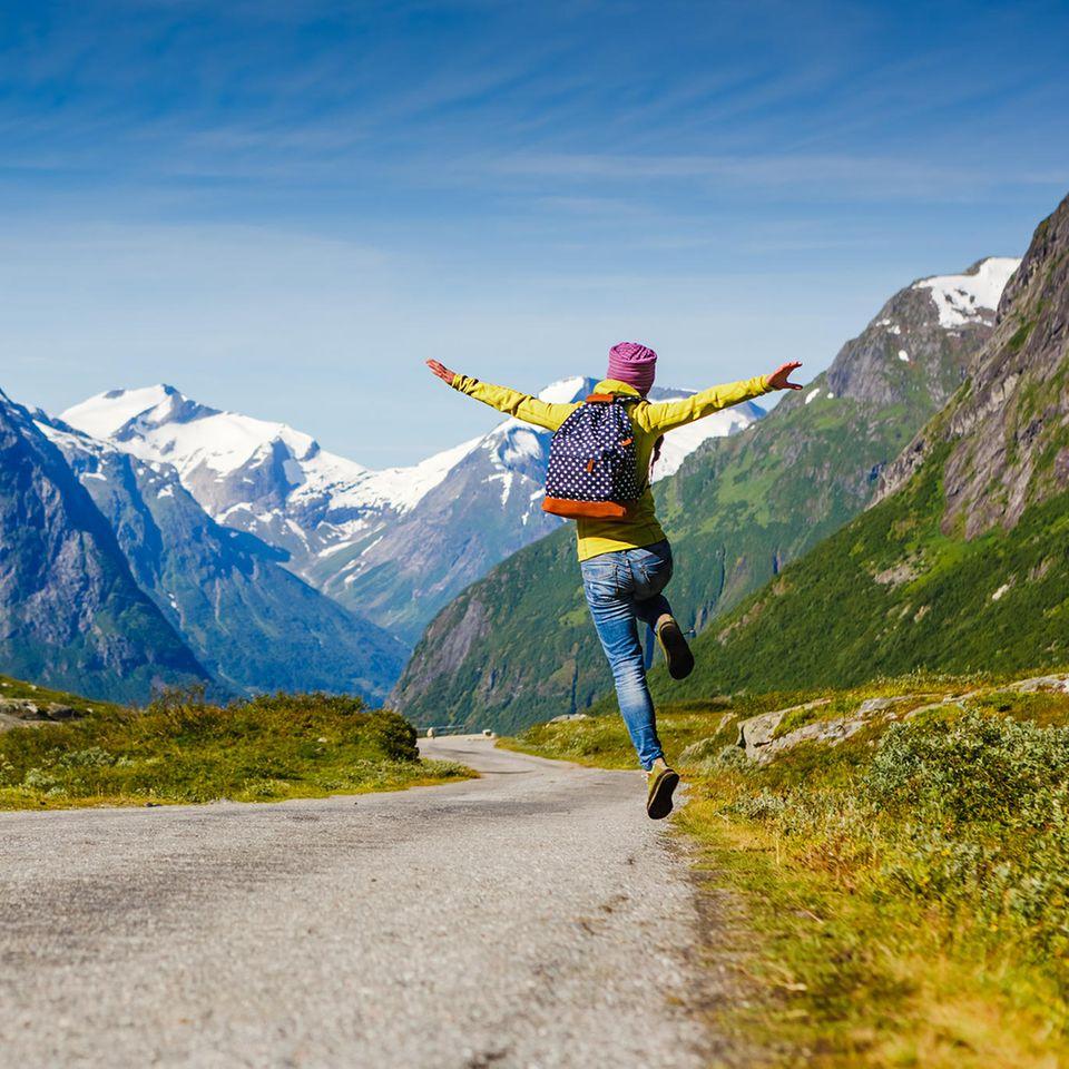 Mikroabenteuer: Frau hüpft auf der Straße, im Hintergrund Berge