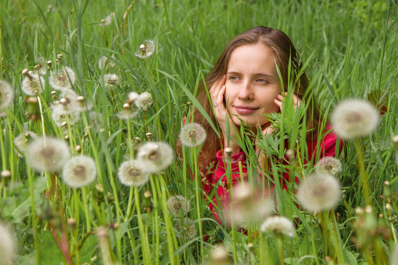 Psychologie: Eine Frau liegt in einer Pusteblumenwiese und denkt nach