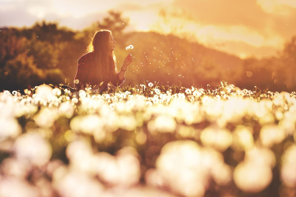 Horoskop: Eine Frau pustet Pusteblume
