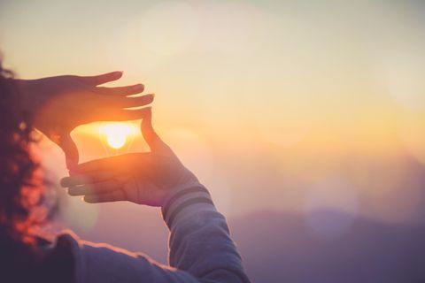 Horoskop: Eine Frau lässt die Sonne durch ihre Hände