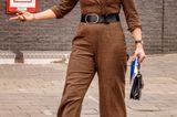 Für den Besuch der Hogeschool in Rotterdam setzt Königin Máxima auf einen eleganten und doch lässigen Look. Zum braunen Woll-Jumpsuit kombiniert die Monarchin einenbreiten Taillengürtel sowie Pumps und Henkeltasche. Das Outfitsteht ihr hervorragend, ein Detail macht Máxima an dem Tag dennoch mächtig zu schaffen.