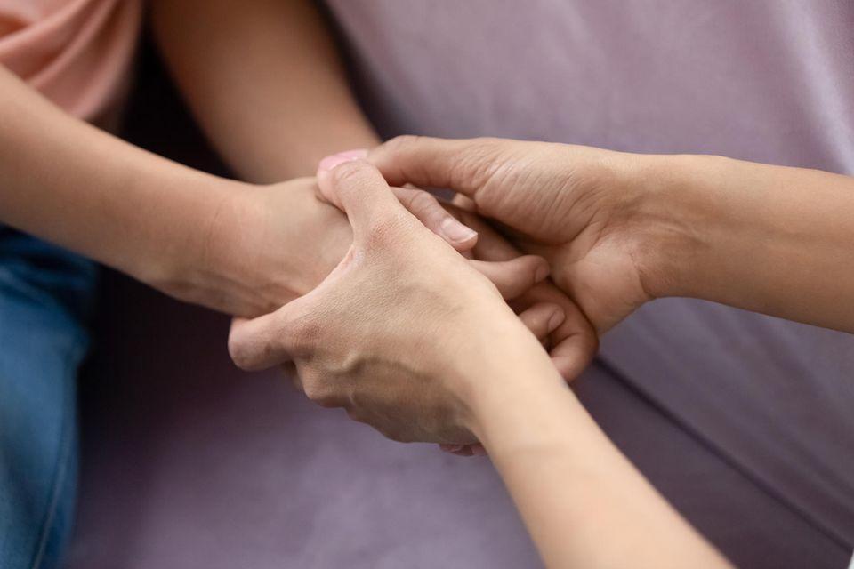 Verzeihen: Zwei Menschen halten einander an den Händen