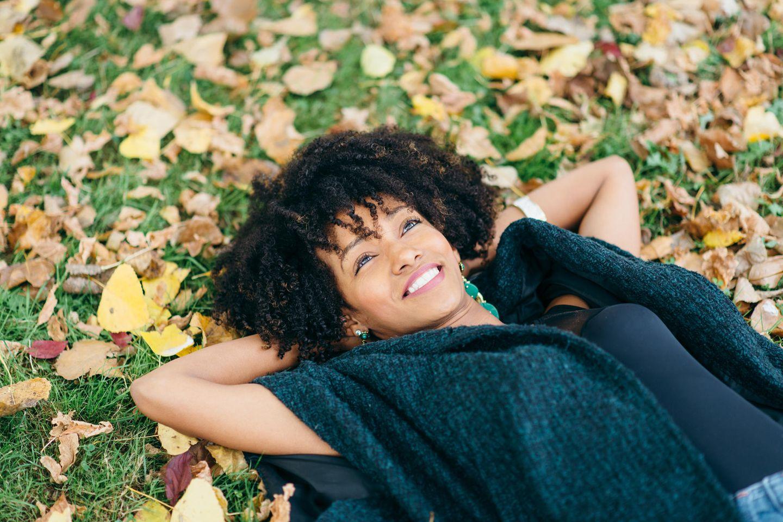 Psychologie: Eine glückliche Frau liegt im Gras und schaut in den Himmel