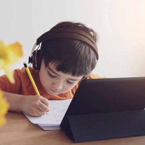 Schüer:innen erzählen: Junge macht Hausaufgaben vor Laptop