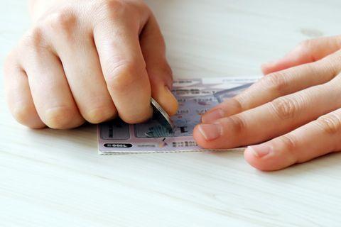 Doppeltes Glück: Hände rubbeln Felder auf Lottoschin frei