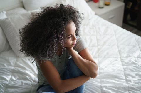 Psychologie: Eine nachdenkliche Frau sitzt auf ihrem Bett