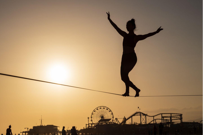 Ausgeglichenheit: Frau balanciert auf Seil