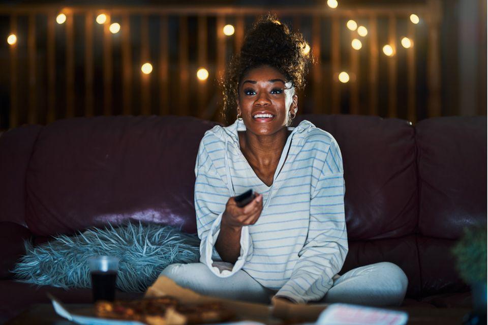 Guilty pleasure: Frau sitzt vor dem Fernseher