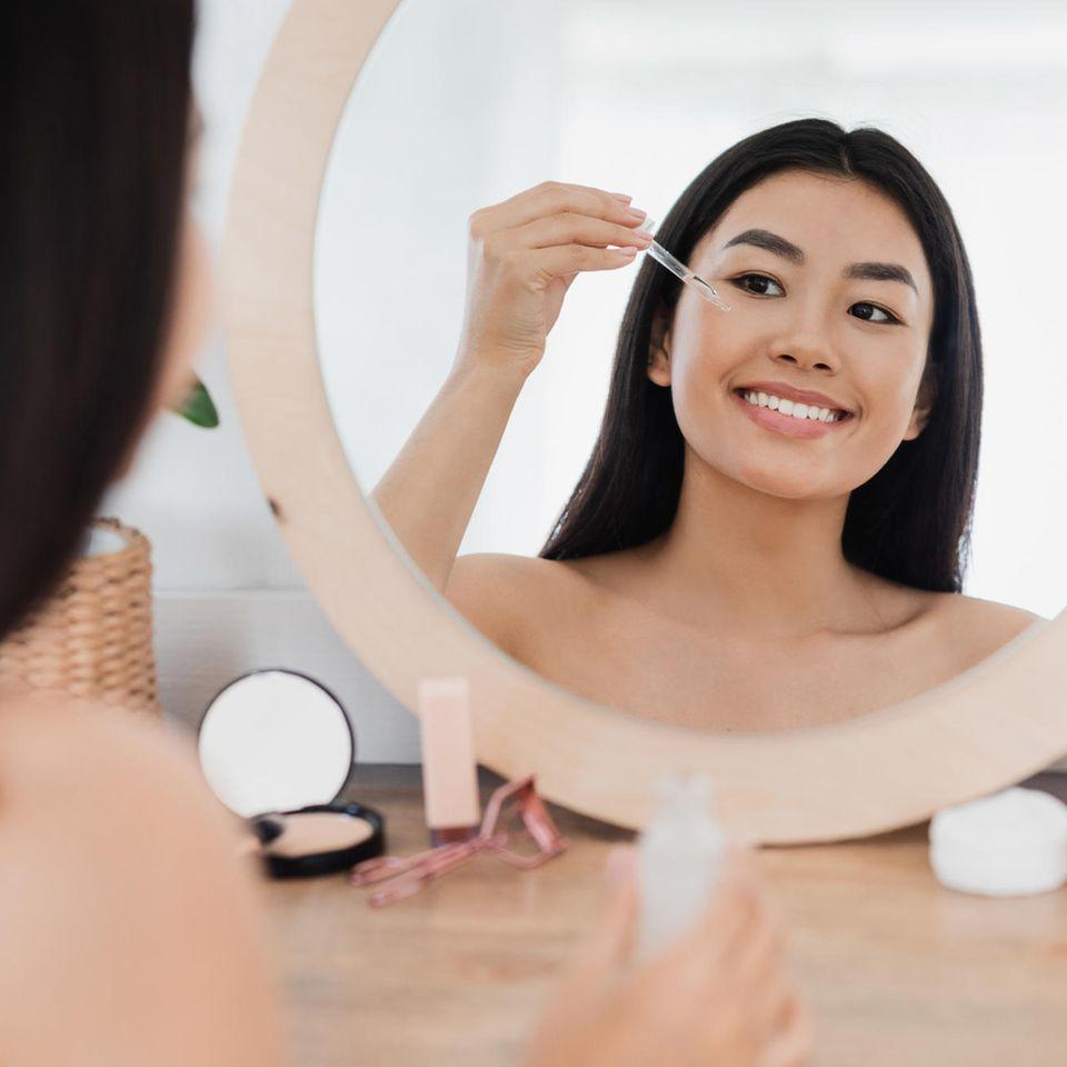 Frau trägt Serum vor Kosmetikspiegel auf das Gesicht auf.