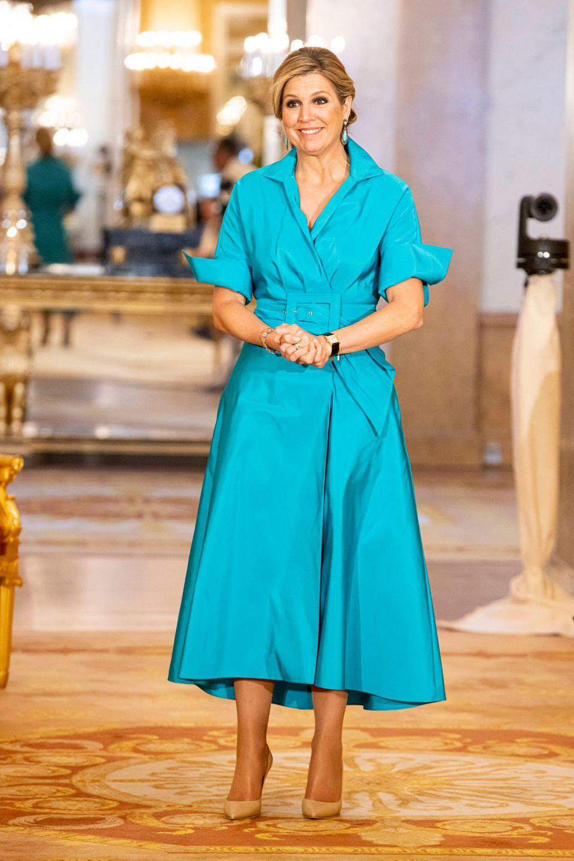 Königin Máxima zeigt sich in einem eleganten Kleid in Bonbon-Blau. Der Taillengürtel sorgt dafür, dass ihre Silhouette erkennbar bleibt und sie nicht untergeht.