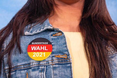 Corona aktuell: Frau mit Bundestags-Wahl-Button an der Jacke