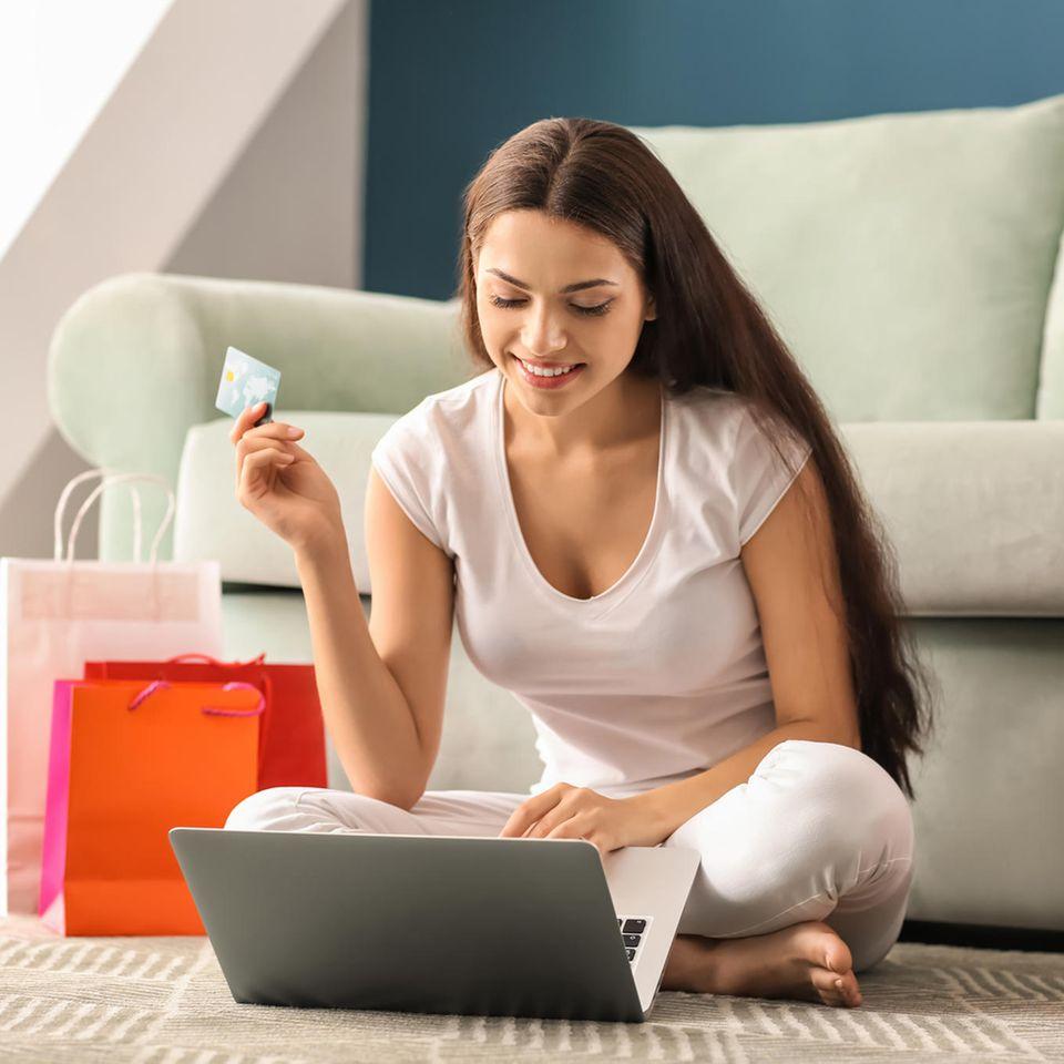 Frau mit Kreditkarte sitzt vor Laptop, Online Shopping